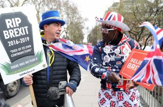 Brexit opponent Steve Bray, left, and Brexit supporter Joseph Afrane walk near the Houses of Parliament in London on March 13, 2019.