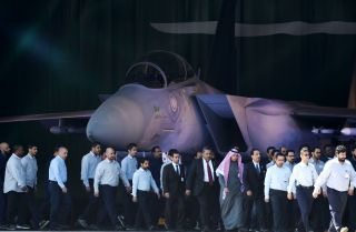 Saudi air force officers and technical staff walk past an advanced F-15SA fighter jet during a ceremony on Jan. 25, 2017 in Riyadh marking the 50th anniversary of the creation of the King Faisal Air Academy.