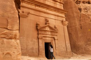 A journalist takes a picture of a tomb at Madain Saleh, a UNESCO World Heritage site, in Saudi Arabia's northwest on March 31, 2018.