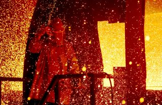 A cloud of molten steel envelopes a worker at a TAMCO Steel, Inc. mill in Rancho Cucamonga, California, in 2002.