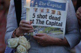 A woman holds a copy of the Capital Gazette newspaper during a candlelight vigil to honor the five people who were killed on June 28, 2018.