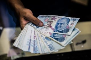 A teller holds Turkish lira banknotes at a currency exchange office in Istanbul on Aug. 13, 2018.
