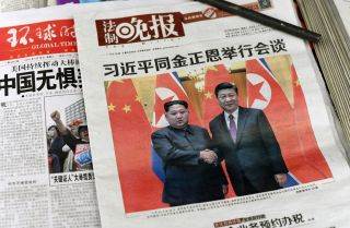 The front page of a March 28, 2018, newspaper in Beijing shows Chinese President Xi Jinping with North Korean leader Kim Jong Un.
