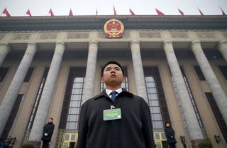 A security guard stands in front of the Great Hall of the People as delegates arrive for a conference in Beijing on March 4, 2016.