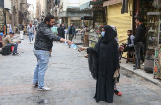 A man provides a pedestrian with hand sanitizer as protection against COVID-19 on the historic Al-Moez street in Cairo, Egypt, on March 23, 2020.