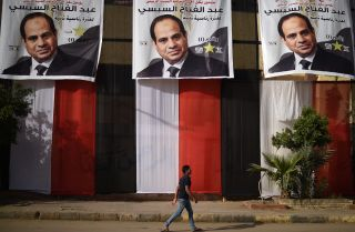 A young Egyptian passes a polling station in Cairo on March 25, 2018, the day before the presidential election kicks off.