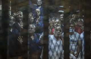 Egyptian Muslim Brotherhood senior members, including Khairat al-Shater (top left), gesture from the defendants' cage at the Egyptian Police Academy on the outskirts of Cairo on June 2, 2015.