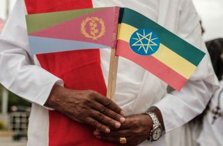 A man holds the flags of Eritrea, left, and Ethiopia as he waits for the arrival of Eritrea's president at an airport in Gondar, northern Ethiopia, on Nov. 9, 2018.
