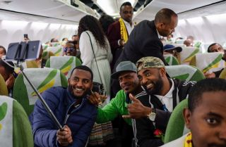 Passengers pose for a selfie inside an Ethiopian Airlines flight on July 18, 2018. The trip was the first commercial flight between the Ethiopian and Eritrean capitals in two decades.