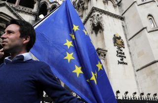 Pro-European Union supporter Phil Jones holds an EU flag outside the entrance to the Royal Courts of Justice, the United Kingdom's High Court, in London on Oct. 13, 2016.