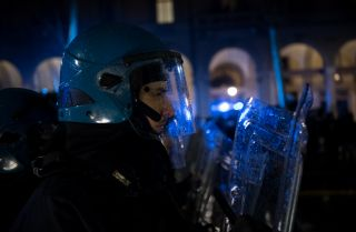 An Italian police officer in riot gear watches an anti-fascist counterdemonstration against a far-right meeting.