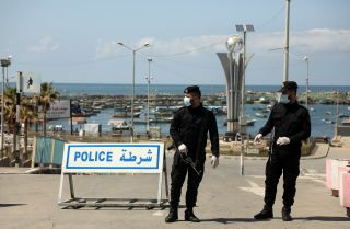Security forces loyal to Hamas wear face masks while they guard the entrance to the seaport in Gaza City on March 25, 2020. The Palestinian city in the Gaza Strip has been on lockdown to stem the spread of COVID-19.