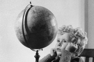A child staring up at a globe and contemplating the world.