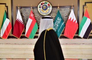 A man walks past the flags of the countries attending the Gulf Cooperation Council summit at Bayan palace in Kuwait City on Dec. 5, 2017.