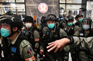 Riot police wear face masks, as a precautionary measure against the COVID-19 coronavirus, as they carry out a crowd dispersal operation in a shopping mall during a protest by pro-democracy supporters in the town of Shatin in Hong Kong on May 1, 2020.