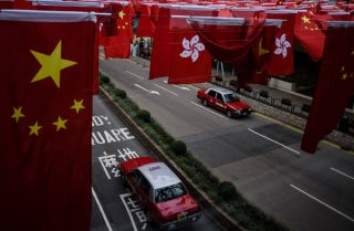 The national flags of China and Hong Kong hang above the street in anticipation of the 20-year anniversary of the handover of the city from the United Kingdom.