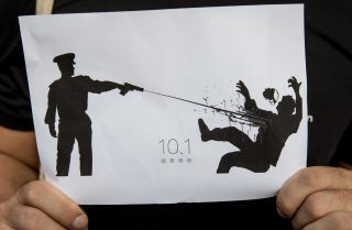 This photo shows a man in Hong Kong holding a drawing depicting the Oct. 1 shooting of a protester by a Hong Kong police officer.