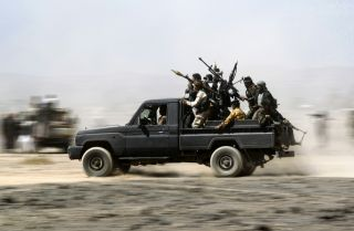 Tribesmen loyal to the Houthis ride in the back of a vehicle during a gathering to mobilize more fighters on Nov. 1, 2016, on the outskirts of Sanaa, Yemen.