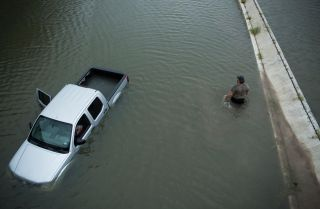 A driver walks past an abandoned truck while checking the depth of an underpass in the aftermath of Hurricane Harvey in Houston, Texas.