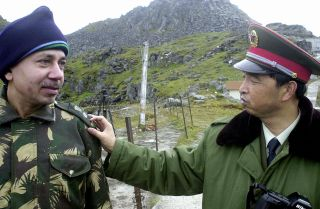 A Chinese soldier interacts with an Indian soldier at the Nathu La Pass area at the India-China border in the northeastern Indian state of Sikkim.