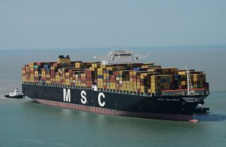 Tugboats maneuver the MSC Valeria as it arrives in Mundra, India, in June 2013.