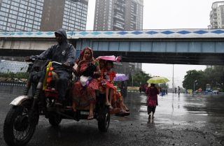 Passengers in Kolkata make their daily commute through a monsoon July 24, 2017.