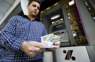 A man withdraws Iranian Rials from an ATM
