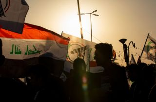 Protesters waving the Iraqi flag alongside one of an armed network march in Basra to denounce U.S. airstrikes that killed dozens of Iraqi militia members.