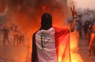 In this photo, an Iraqi protester flashes the V sign during an anti-government demonstration in Baghdad on Oct. 2, 2019.