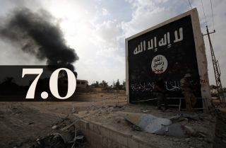 Iraqi fighters enter the city of Qaim on Nov. 3 near a wall bearing an image of the Islamic State flag.