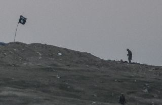 Militants of Islamic State are seen just before the explosion of airstrike on Tilsehir hill near the Turkish border on Oct. 23, 2014, at Yumurtalik village, in Sanliurfa province.