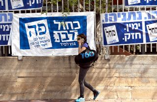 This photo shows a woman walking past election banners in Tel Aviv during Israel's elections on April 9, 2019.