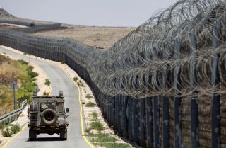 An Israeli army vehicle drives on the road along the border fence that separates the Israeli-annexed Golan Heights and Syria on July 19, 2017.