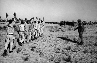 Egyptian prisoners of war holding their hands aloft after being rounded up by Israeli forces in the Sinai Desert following the Six-Day War in 1967.
