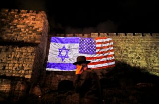 The U.S. and Israeli flags mingle in an image projected on the walls of Jerusalem's Old City.