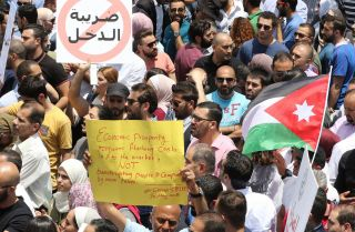 A bill designed to reduce Jordan's debt by increasing income taxes has sparked large protests in country.