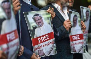 Protestors hold posters of missing journalist Jamal Khashoggi