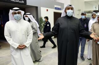 Kuwaiti Health Minister Sheikh Basel al-Sabah, right, speaks with the media on Feb. 22, 2020, as officials at the Kuwait City airport prepare to take Kuwaitis returning from Iran to a hospital to be tested for the COVID-19 virus.