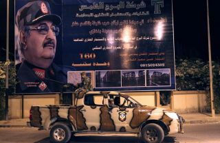 Members of the Libyan Special Forces, who are loyal to Khalifa Hifter, ride in a pickup truck past a billboard bearing the strongman's image in Benghazi during September 2017.