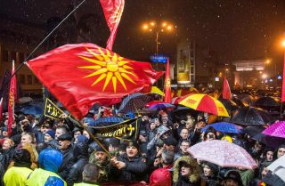 Demonstrators hold Macedonian flags during a protest