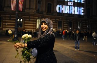 A woman holds a white rose near the Toulouse capital building in Jan. 2015 beneath a motto of solidarity for the victims of the Charlie Hebdo attacks.
