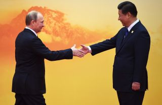 Russian President Vladimir Putin (L) shakes hands with Chinese President Xi Jinping.