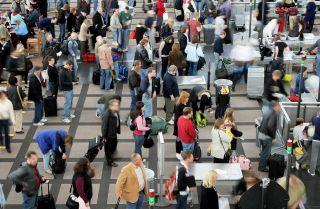 Travelers move through a security line at Denver International Airport the day before Thanksgiving. But remarkably, many Americans insist that they have little to be thankful for.