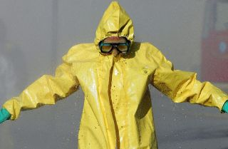 A man in a hazardous materials suit goes through a decontamination shower during a WMD training workshop in California.