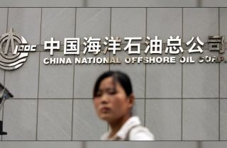 A woman walks past the headquarters of the state-run energy firm China National Offshore Oil Corp. in Beijing.