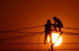 Indian workers adjust electricity cables ahead of the Kumbh Mela festival on Dec. 26, 2015.