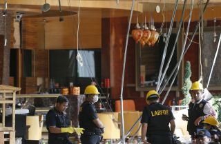 Indonesian forensic investigators scour the site of a bombing at the Ritz-Carlton hotel in Jakarta on July 18, 2009. An employee of a shop in the hotel facilitated the attack.