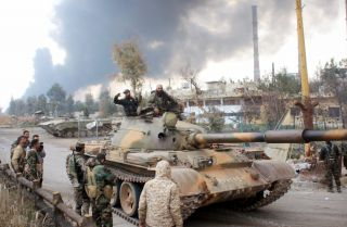 Syrian government forces patrol near Aleppo's thermal power plant after they took control of the area on the eastern outskirts of Syria's northern embattled city from Islamic State (IS) group fighters on February 21, 2016. In two days Syrian government forces have taken more than a dozen villages from IS jihadists around a stretch of highway that runs east from the northern city of Aleppo to the Kweyris military base. / AFP / GEORGE OURFALIAN (Photo credit should read GEORGE OURFALIAN/AFP/Getty Images)
