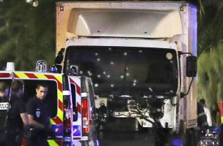 Police officers stand near the truck used to plow through a crowd in Nice, France, on July 14. Based on the rampage's success, the Islamic State's Rumiyah magazine has encouraged the group's followers to conduct more attacks using large, paneled trucks.
