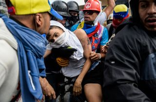 Protesters help a demonstrator who was run over by a National Guard vehicle during a protest against Venezuelan President Nicolas Maduro, whose government is desperately clinging to power.